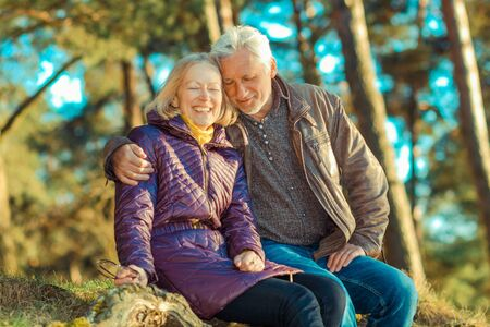 grandpa and grandma: Beautiful elderly couple embracing and enjoying life in the forest at sunset. couple of grandparents embracing Stock Photo