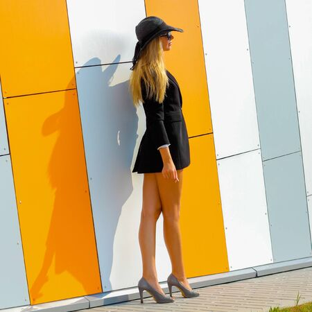 the caucasian beauty: beautiful attractive trendy girl in long-skirted hat posing on the background orange wall Stock Photo