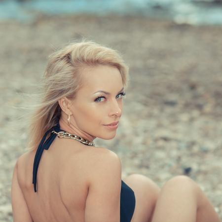 fille sexy: Fermer portrait de la mode jeune fille blonde en maillot de bain. Jolie jeune femme bronz�e sexy en bikini posant sur le bord de mer de pierre Banque d'images