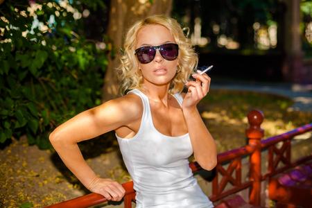 femme chatain: Close-up d'une femme sexy en chemise blanche et des lunettes de soleil de fumer le cigare