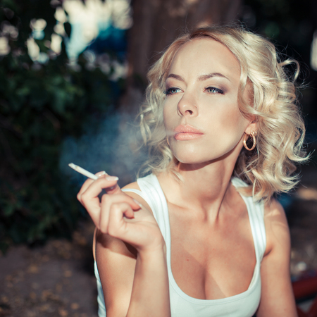 cigar smoking woman: Close-up of sexy woman in sunglasses and white shirt smoking cigar