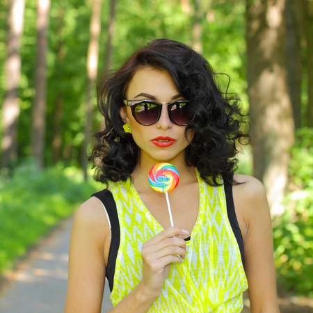 sucking lollipop: colorful portrait of young sexy funny fashion girl posing  in summer style outfit with red lollipop wearing blue jeans and  t-short. Young sexy girl sucking lollipop. Outdoors, lifestyle. Archivio Fotografico