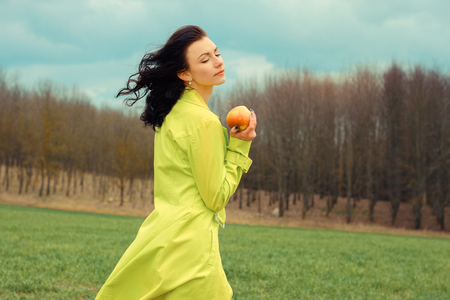 eyes shut: outside portrait of beautiful young curly woman with eyes shut with red apple in park. Young woman eating apple, outdoors