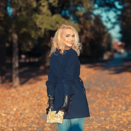 gift spending: Happy young woman holding a small present box. Happy and positive young blond woman with a gift on outdoor autumn
