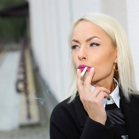 sexy blonde woman: Portrait of a business woman nervously smoking Stock Photo