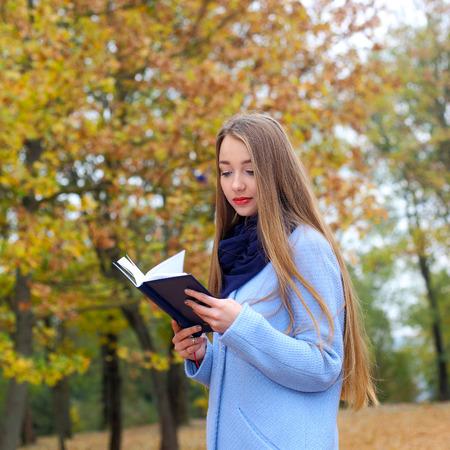 romantic dreamy girl reading a book outdoors. Stock Photo - 50922562