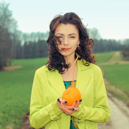 shut: outside portrait of beautiful young curly woman with eyes shut with red apple in park. Young woman eating apple, outdoors