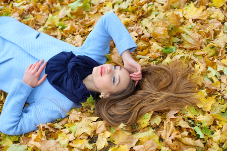 cryptic: pretty sad dreamy girl lying among the leaves in the park