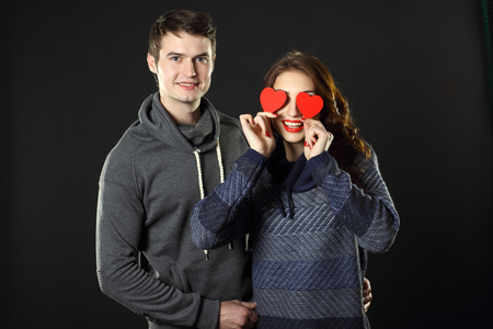 flirtation: Ordinary beautiful couple having fun with a paper hearts on Valentines Day. On a black background. Stock Photo
