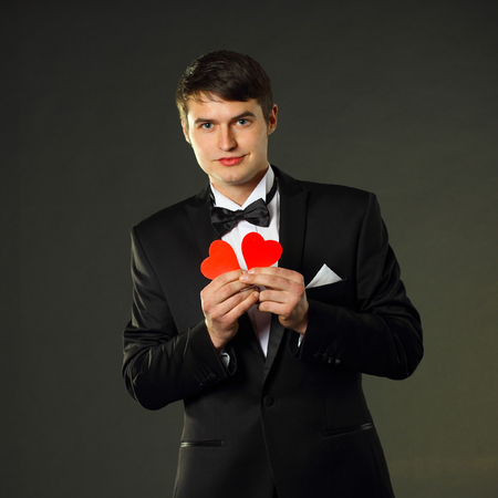 nice handsome man in a tuxedo with a red paper hearts. On a black background.