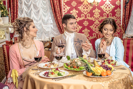 richly: company in the historic vintage clothing have fun in a richly served restaurant. Retro company portrait. Romantic Beauty.Vintage Styled
