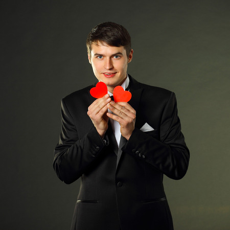 gigolo: nice handsome man in a tuxedo with a red paper hearts. On a black background.