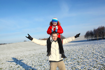 having fun in winter time: happy young father and his little son spending time outdoor in winter park. Son sits on his fathers shoulders and having fun
