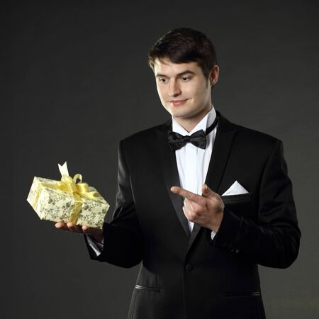 nice handsome man in a tuxedo gives a gift. On a black background. Stock Photo