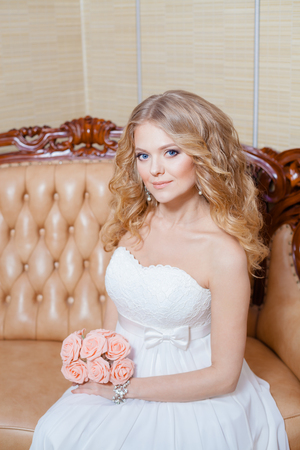 catalogs: blonde bride in vintage interior. The beautiful woman posing in a wedding dress