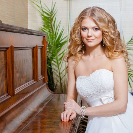 catalogs: blonde bride in vintage interior. The beautiful woman posing in a wedding dress. Bride with vintage piano