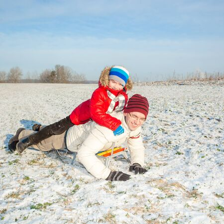 sledging people: happy family in winter. Dad and son having fun in the winter Stock Photo