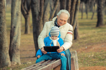 narrator: Grandfather and grandson are looking tablet on bench outdoors