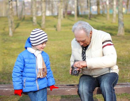 grandfather: Abuelo con su nieto el estudio de c�mara de formato medio de la vendimia. Abuelo muestra nieto c�mara retro