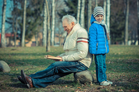 grandson: Grandfather and grandson reading a book outdoors