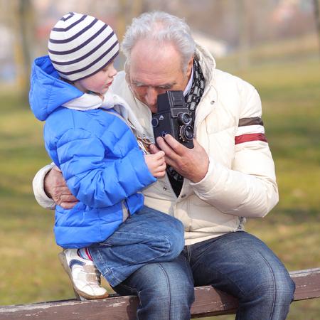 narrator: Grandfather with his grandson studying vintage medium format camera. Grandfather shows grandson retro camera