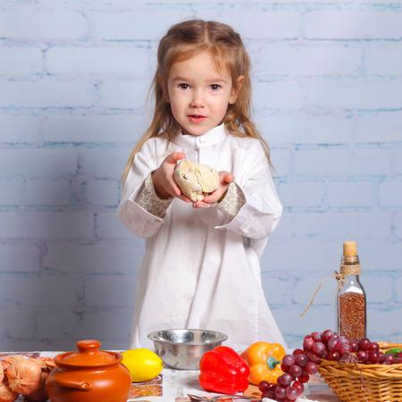 little dough: Little girl preparing dough for bread. Cute little girl in the kitchen preparing cookies. child chef Stock Photo