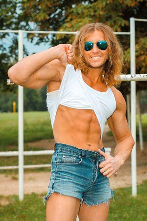 hombre fuerte: caucásico encajar a hombre sexy en gafas de sol posando Bares cerca Deportes Al Aire Libre. Hombre fuerte y confiado outdoor presentación