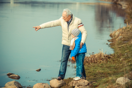 curiosity: Grandfather and grandson are crossing the river on the stones Stock Photo