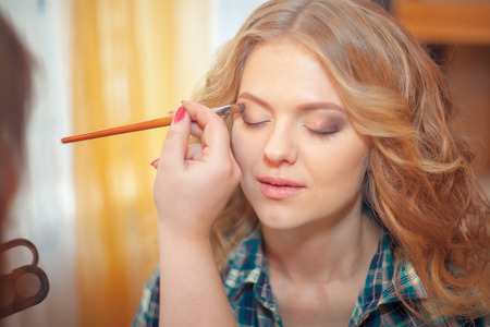 make up artist: make up artist doing professional make up of young woman Stock Photo