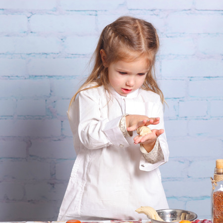 preparing dough: Little girl preparing dough for bread. Cute little girl in the kitchen preparing cookies. child chef Stock Photo