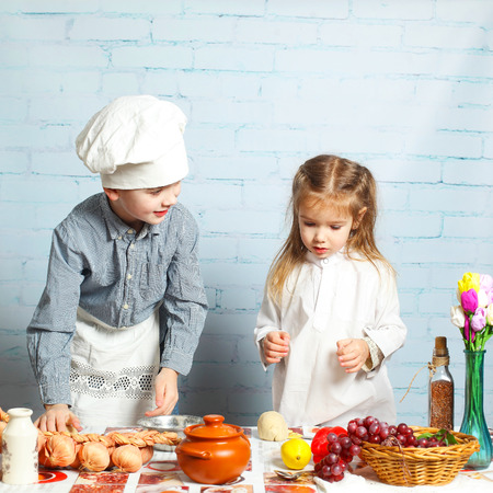 little dough: Children chefs. little brother and sister cook in the kitchen. Little boy preparing dough for bread.
