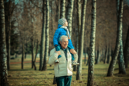 grandad: Grandfather carries grandson on his shoulders