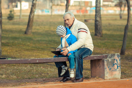 graying: Grandfather and grandson are looking tablet on bench outdoors