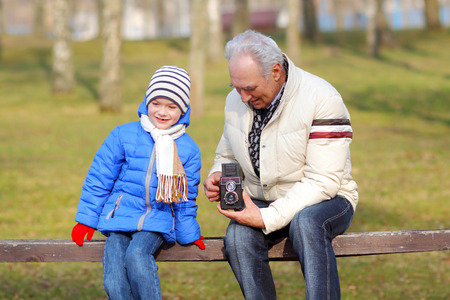 grandfather and grandson: Grandfather with his grandson studying vintage medium format camera. Grandfather shows grandson retro camera