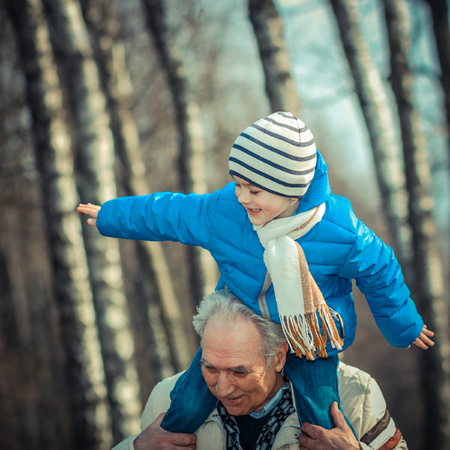 grandson: Grandfather carries grandson on his shoulders