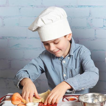 little dough: Little boy preparing dough for bread. Cute little boy in the kitchen preparing cookies. child chef Stock Photo