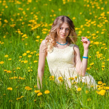 enjoys: Beautiful girl on the field of dandelions is happy and enjoys the sun. sexy blonde in the spring