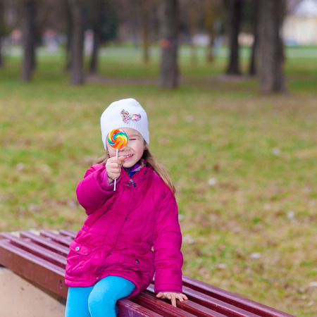 portrait of young funny little girl with lollipop. Young girl sucking lollipop. Outdoors, lifestyle. positive and cheerful  little girl