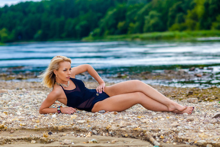 stony: girl in a black bikini swimsuit on the stony beach. Sexy blonde woman sunbathing