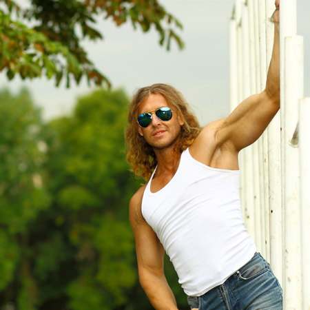 sexy caucasian fit man in sunglasses posing near Sports Bars Outdoors. muscular man posing outdoor Stock Photo