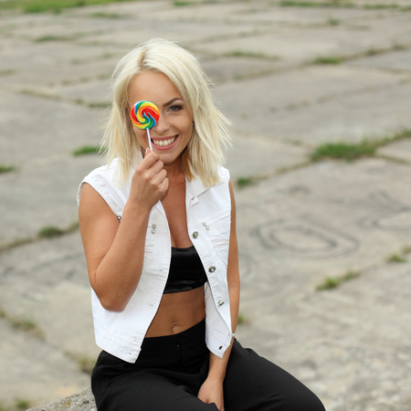 sucking lollipop: portrait of young sexy funny fashion girl with red lollipop. Young sexy girl sucking lollipop. Outdoors, lifestyle. positive and cheerful  hipster girl