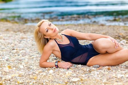 girl in a black bikini swimsuit on the stony beach. Sexy blonde woman sunbathing