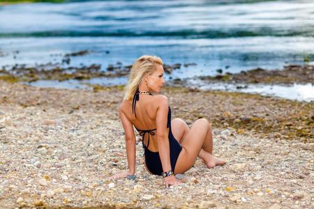 sexual position: girl in a black bikini swimsuit on the stony beach. Sexy blonde woman sunbathing