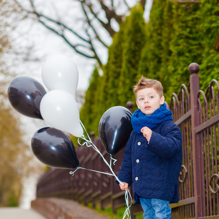 dreaminess: happy little Boy, outdoor. Trendy little boy with balloons Stock Photo