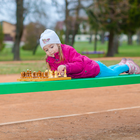 pensamiento estrategico: Little Girl playing chess outdoors on a park bench