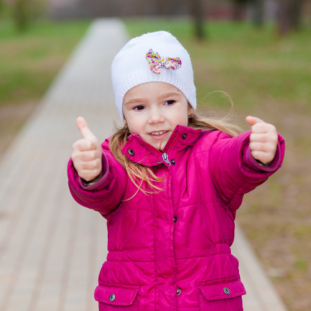 puts: Young girl puts her big thumbs up. Portrait of cheerful kid. Smiling girl having fun outside. Happy successful person.