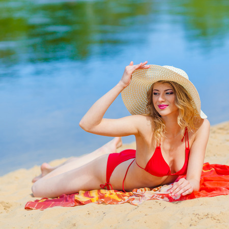girl in a red bikini sunbathing on the beach. Sexy blonde woman sunbathing by the sea