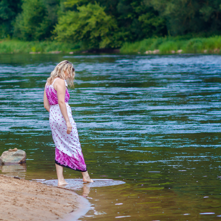 Woman in a long dress on the shore near the water