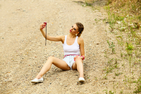 cocky: hipster girl in shorts and t-shirt sitting on the ground and makes selfie