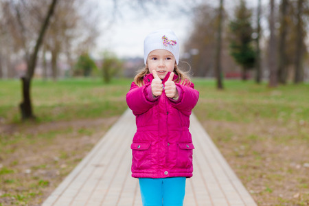 sm: Young girl puts her big thumbs up. Portrait of cheerful kid. Smiling girl having fun outside. Happy successful person.
